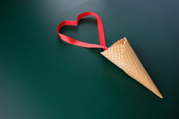 Wafelkegel met valentijnskaartelementen op donkere achtergrond. valentijnsdag concept. rood lint in de vorm van hart. valentijnsdag