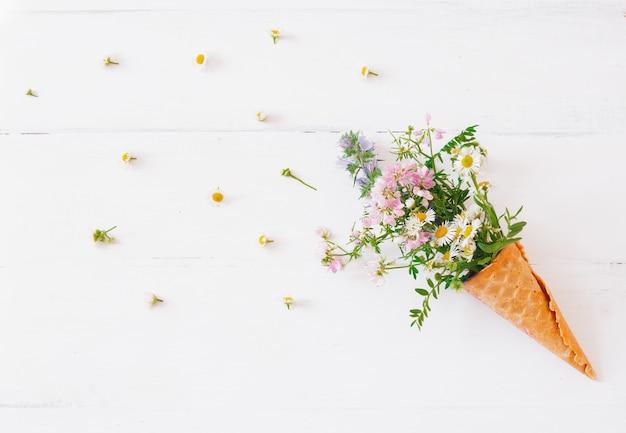 Wafelkegel met wilde bloemen op wit