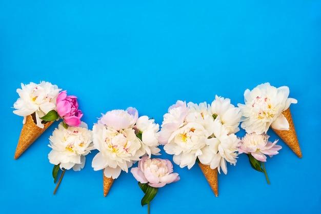 Wafelroomijskegel met witte pioenbloemen op blauwe achtergrond.