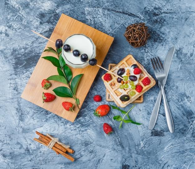 Wafels en fruit met melk, pruimen met stokjes, kaneelstokjes en aardbeien