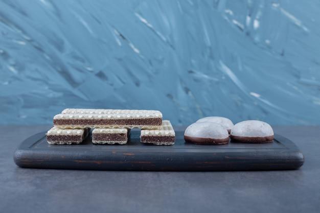 Wafels en popcakes op een houten dienblad op marmeren tafel.