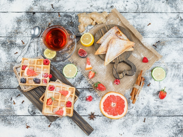 Wafels en thee op houten bord met bessen en citrus