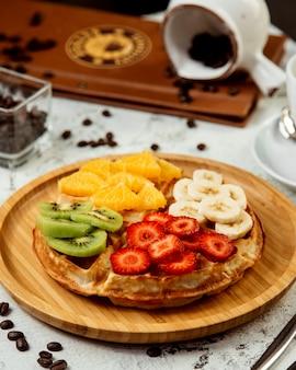 Wafels gegarneerd met gemengd gesneden fruit