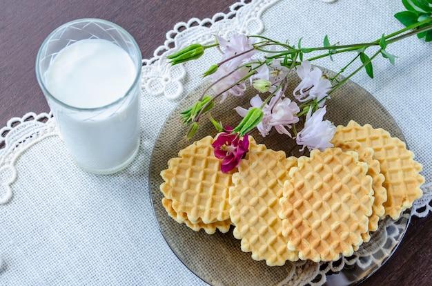 Wafels met aquilegia-bloemen en een glas melk