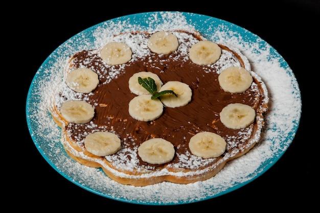 Wafels met chocolade en banaan op een zwarte achtergrond.