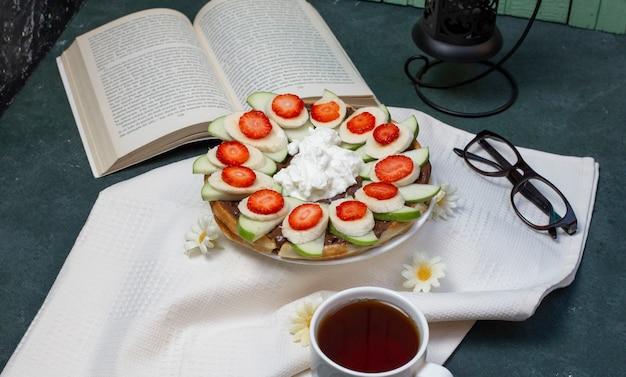 Wafels met gesneden banaan, aardbeien en slagroom