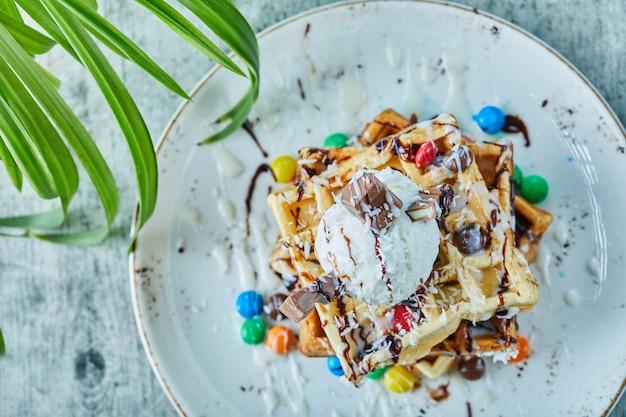 Wafels met ijs, snoep, chocolade in de witte plaat op het bladoppervlak