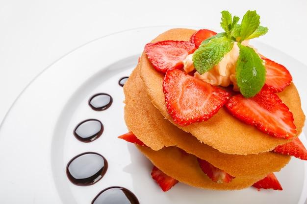 Wafels met karamelsaus, slagroom en aardbeien die op witte achtergrond worden geïsoleerd