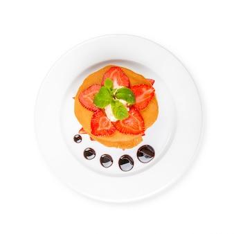 Wafels met karamelsaus, slagroom en aardbeien op witte achtergrond worden geïsoleerd die
