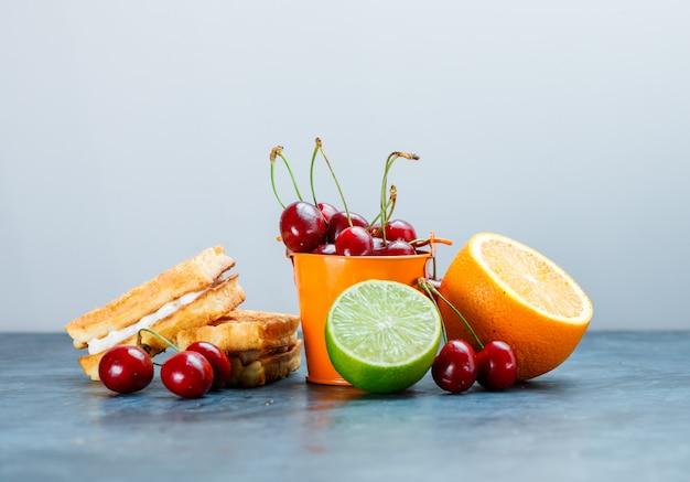 Wafels met kersen, sinaasappel, limoen zijaanzicht op grungy blauwe en witte achtergrond