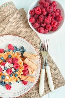 Wafels met verse banaan, frambozen, bosbessen voor het ontbijt. verse wafels met fruit. lichte houten achtergrond. zomer zelfgemaakt ontbijt. ruimte kopiëren. de balans van gezond eten.