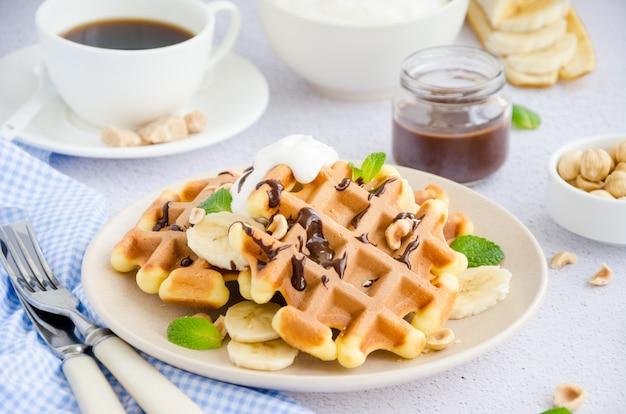 Wafels met verse banaan, hazelnoten, chocoladesaus en slagroom op een bord