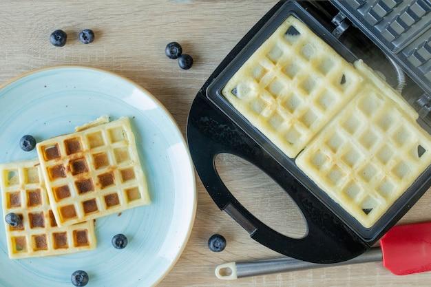 Wafels worden gebakken in de wafelijzer. hartige wafels. ontbijt concept