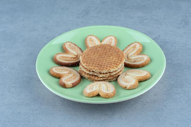 Wafelschijfjes met koekjes op groene plaat.
