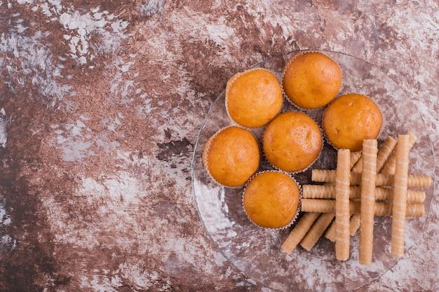 Wafelstokjes en cupcakes in een glazen schotel op het marmer, bovenaanzicht