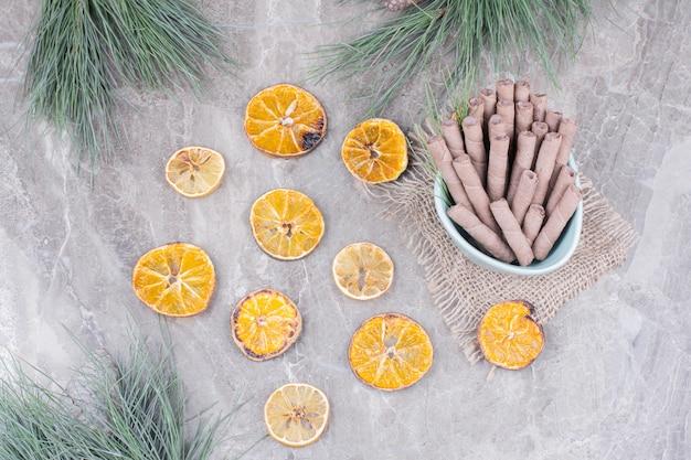 Wafelstokjes in een blauwe beker met droge stukjes sinaasappel eromheen.