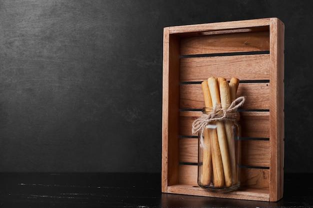 Wafelstokjes in een glazen pot in een houten dienblad.
