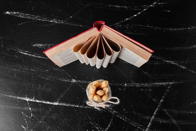 Wafelstokjes in een glazen pot met een boek opzij.