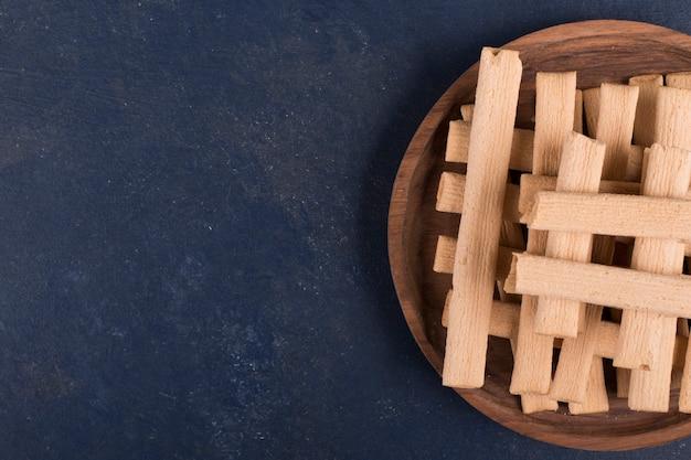Wafelstokjes in een stapel in een houten schaal aan de rechterkant