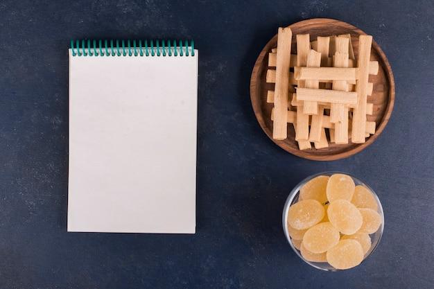Wafelstokjes in een stapel in een houten schaal met een kookboek opzij