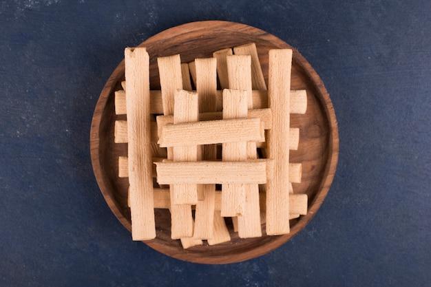 Wafelstokjes in een stapel in een houten schotel, bovenaanzicht