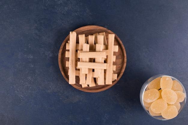 Wafelstokjes in een stapel in een houten schotel met jam opzij