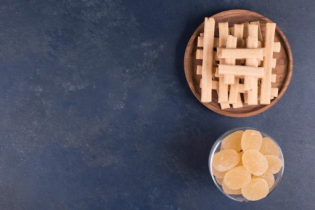 Wafelstokjes in een stapel met marmelades in een glazen beker