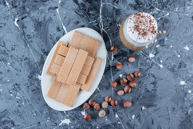 Wafelstokjes met macadamia-noten en een glazen kopje lekkere warme koffie.