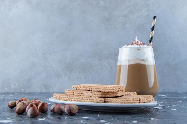 Wafelstokjes met macadamianoten en een glazen kop lekkere warme koffie.