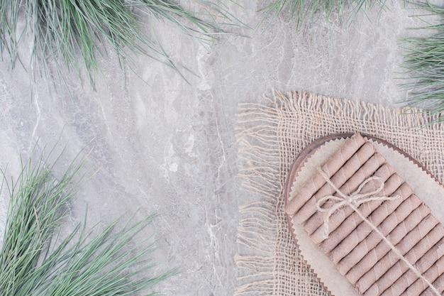 Wafelstokken op houten schotel op rustiek.