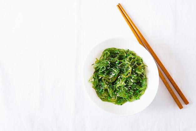 Wakame chuka of zeewiersalade met sesamzaden in kom op witte lijst. traditioneel japans eten. bovenaanzicht. plat liggen