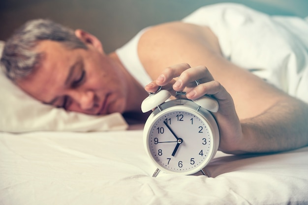 Wakker geworden. hand schakelt de wekker uit in de ochtend. zachte huidtoon. uitgeputte man wordt wakker gewekt door een wekker in zijn slaapkamer