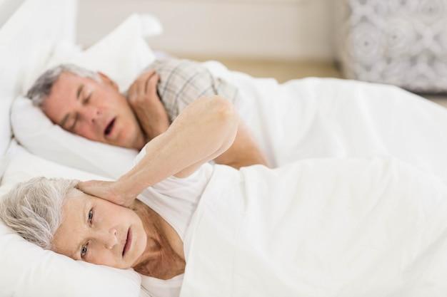 Wakker senior vrouw in bed over haar oren terwijl haar man snurkt