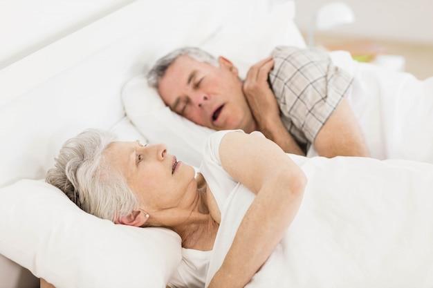 Wakker senior vrouw in bed terwijl haar man snurkt