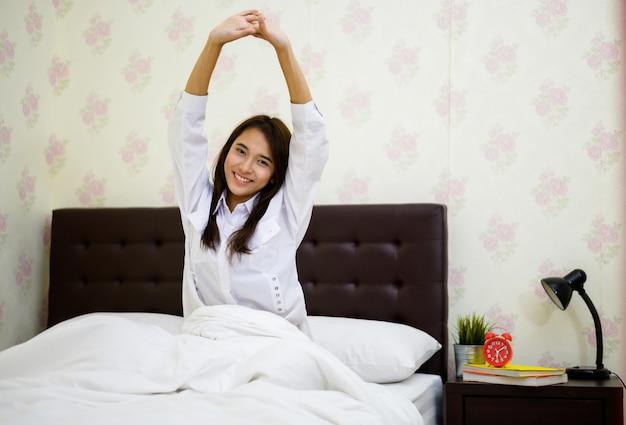 Wakker worden: vrouw wordt 's ochtends wakker op het bed