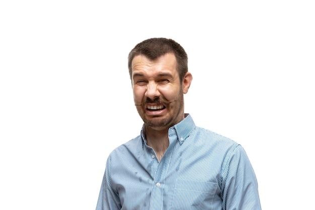 Walgelijk. jonge man met grappige, ongebruikelijke populaire emoties en gebaren geïsoleerd op een witte studio achtergrond. menselijke emoties, gezichtsuitdrukking, verkoop, advertentieconcept. trendy look geïnspireerd op memes.