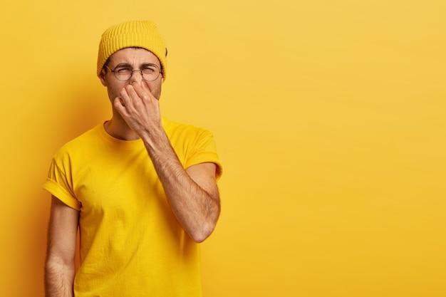 Walgt jonge hipster wringt neus met vingers, kijkt walgend als iets stinkt, bril, gele hoed draagt