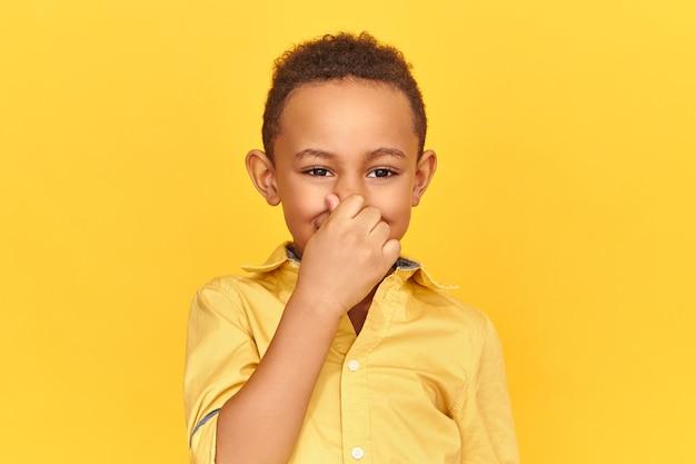 Walgt ontevreden jongen met donkere huid, neus dichtknijpen met vingers, adem vasthouden vanwege onaangename grove stank van zweterige oksels of vuile sokken