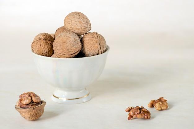 Walnoot in een schaal worden gestapeld in een witte kop. volgende gepelde noten. plantaardig eiwit is een analoog van een dier