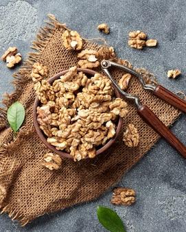 Walnoot kernels in klei kom. noten en notenkraker op grijs