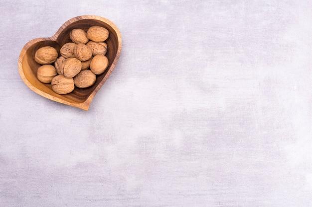 Walnoot op een bord in de vorm van een hart op grijze tafel achtergrond