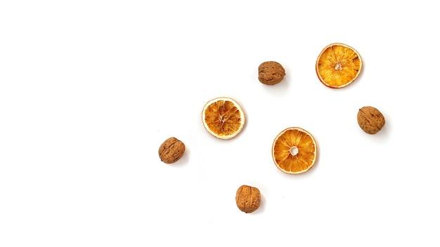 Walnoten en droge sinaasappelen op witte achtergrond - bovenaanzicht