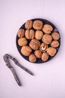 Walnoten heap eten met half gepelde noten in zwarte plaat in de buurt van vintage notenkraker op witte achtergrond, bovenaanzicht, gezond voedsel concept