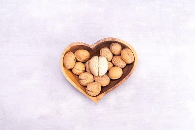 Walnoten houden van gezond hersenvoedsel. de vorm van het menselijk brein is omgeven door walnootpitten in de vorm van een hart
