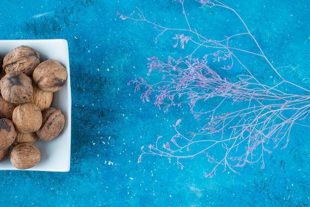 Walnoten in de schaal in een kom, op de blauwe tafel.
