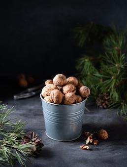 Walnoten in een metalen pot op een donkere houten tafel onder groene kerstboom. vooraanzicht en kopieerruimte