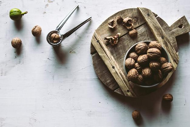 Walnoten in houten kom op tafel met notenkraker.