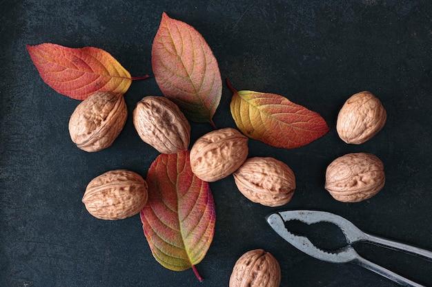 Walnoten met en zonder schelpen en notenkraker op donkere tafel met herfstbladeren
