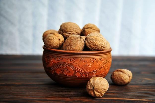 Walnoten, noten in aardewerk op een houten tafel. zijaanzicht