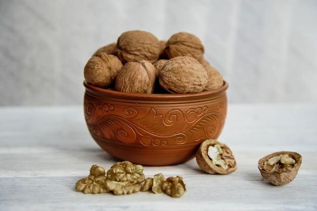 Walnoten, noten in aardewerk op een witte tafel. zijaanzicht
